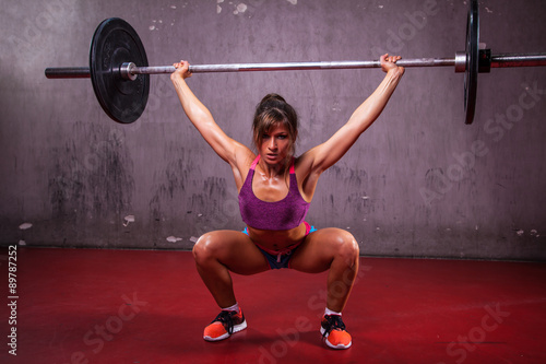 Fotografía  Muscular girl running overheads in the gym.