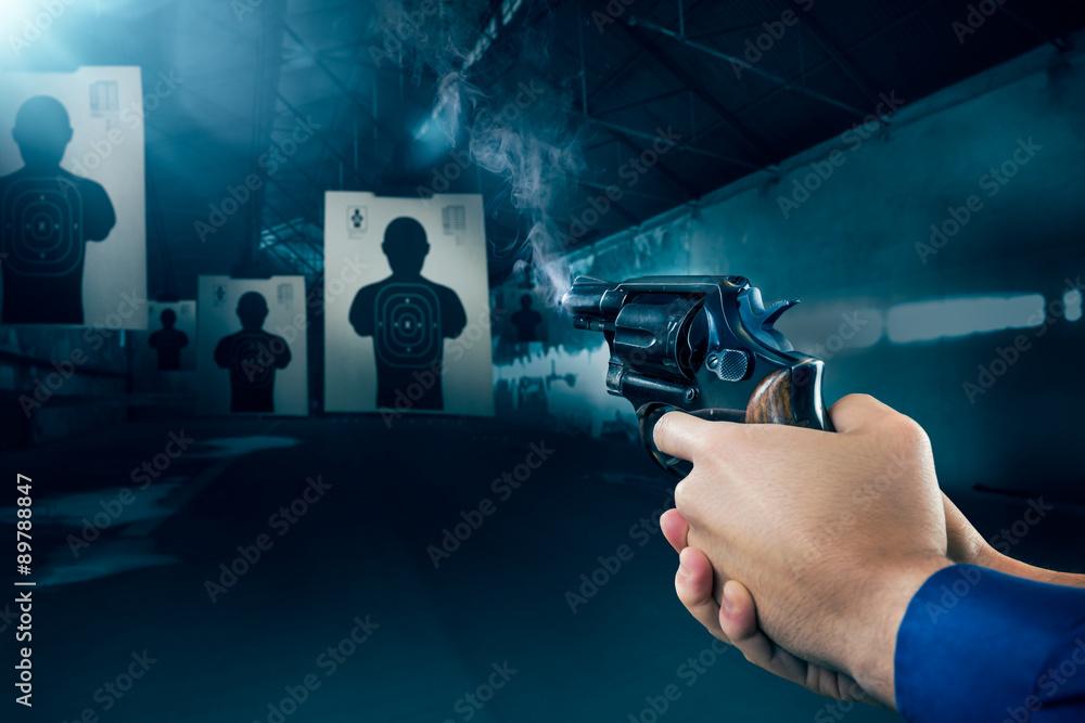 Fototapety, obrazy: Police officer firing a gun at a shooting range / dramatic light