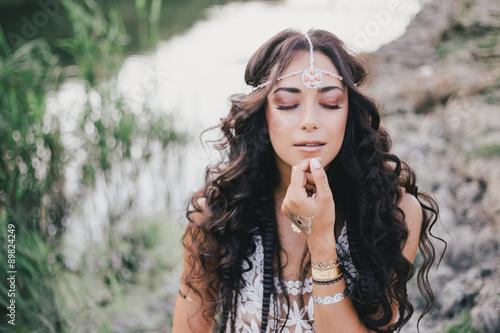 фотография  Beautiful young woman with long curly hair dressed in boho style dress posing ne