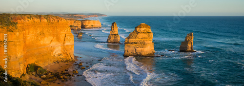 Panoramic image of the landmark Twelve Apostles along the famous Great Ocean Road, Victoria, Australia glowing yellow at sunset