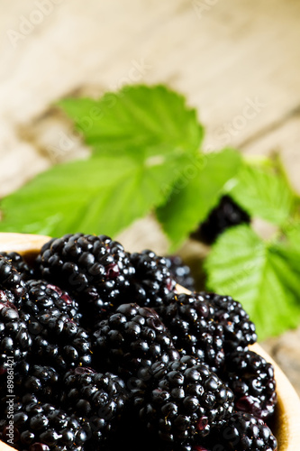 Fényképezés  Fresh blackberries with leaves in a wooden bowl, selective focus