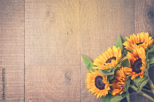 In de dag Zonnebloem Autumn background with sunflowers on wooden table. View from above. Retro filter effect