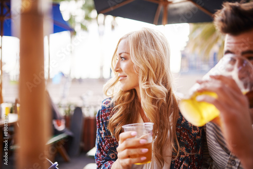 Fotografiet woman with her boyfriend enjoying drinking a beer at outdoor beach side bar or p