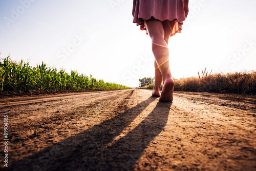 woman goes barefoot at sunset on field road Wallpaper Mural