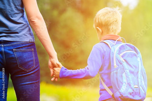 Fényképezés  Mother holding hand of little son with backpack outdoors