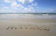 "Word ""WEEKEND"" handwritten in sand on a beach"