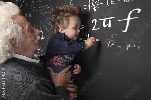 Photo  Nonno scienziato con nipotino in braccio che scrive alla lavagna