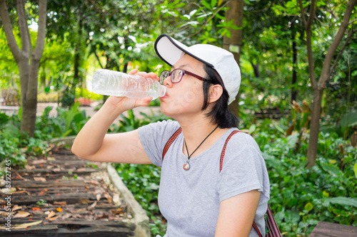 Photo  Asian woman drinking water in the park