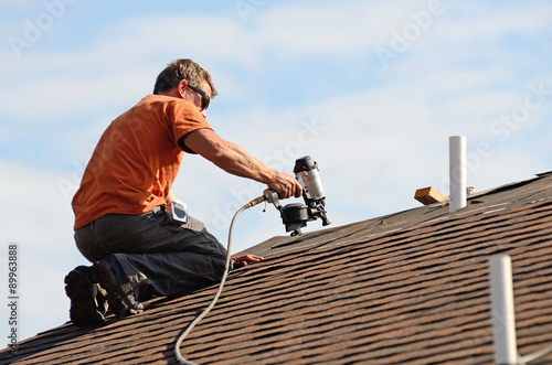 Fotografie, Obraz  Building contractor putting the asphalt roofing on a large commercial apartment building