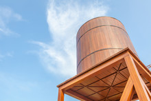 Retro Style  Wooden Water Tower Over The Blue Sky Background.