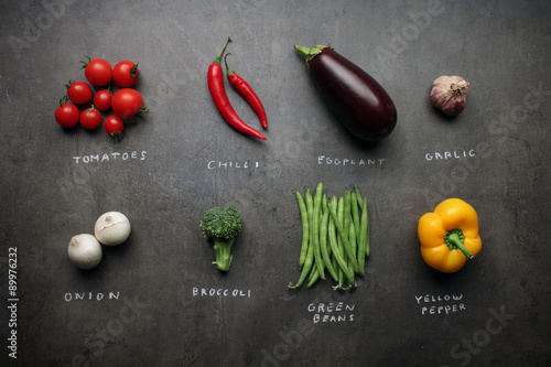 Fotografía  Fresh vegetables with chalky signs on grey kitchen table