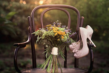 Beautiful Wedding Shoes With High Heels And A Bouquet Of Colorful Flowers On A Vintage Chair On The Nature In Sunset Light, Decorations, Preparing For The Wedding, Details, Boudoir