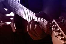Playing Guitar On Purple And Orange Light
