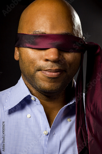 Fotografie, Obraz  Black businessman blindfolded to represent corporate uncertainty