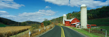 This Is A Country Road With A Farm On The Right Hand Side Of The Road. It Has A Red Barn And Silo.