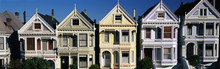 These Are The Historic Victorian Homes On Steiner Street. They Are All Painted In Pastel Colors. They All Have A Pointed Gable At The Top Of Each House And A Small Balcony On The Second Floor. There Is A Blue Sky.