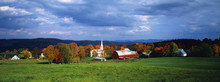 This Is A View Of The Village In Autumn. There Is A Typical New England White Church With A Tall Steeple And A Red Barn. There Is A Vast Green Field In Front Of The View Of The Village With Fall Foliage In The Village.