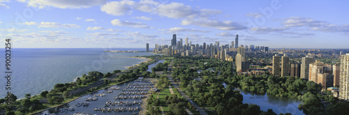 This shows Lincoln Park, Diversey Harbor with its moored boats, Lake Michigan to the left and the skyline in summer. There is morning light on the city.