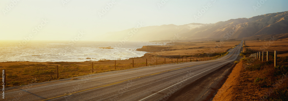 Fototapety, obrazy: This is Route 1also known as the Pacific Coast Highway. The road is situated next to the ocean with the mountains in the distance. The road goes off into infinity into the sunset.
