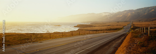 Photo sur Aluminium Cote This is Route 1also known as the Pacific Coast Highway. The road is situated next to the ocean with the mountains in the distance. The road goes off into infinity into the sunset.
