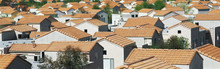 This Is A Housing Development In A Southern California Desert Community. The Houses Have Reddish Orange Spanish Tile Roofs. They Are Situated Very Close To Each Other And They All Look Identical. There Are A Few Trees In Between The Homes.