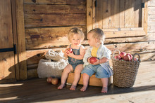Baby Girl And Baby Boy Sitting In A Wooden Box And Eating Apples