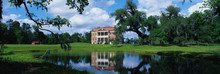 This Is A Southern Plantation Called Drayton Hall. It Is A Pre-Revolutionary Plantation Set On The Ashley River. It Has Georgian Palladian Architecture And Was Built From 1738-1742. It Is Set Back On A Green Lawn With A Pond Showing The Reflection Of The Plantation In The Water.