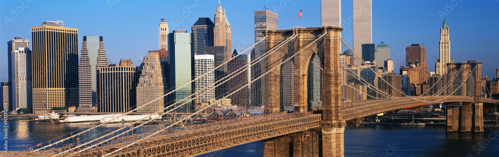 Fototapety, obrazy: This is a close up of the Brooklyn Bridge over the East River. The Manhattan skyline is behind it at sunrise.
