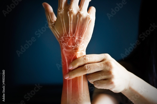 Fotografia  Acute pain in a woman wrist, colored in red on dark blue background