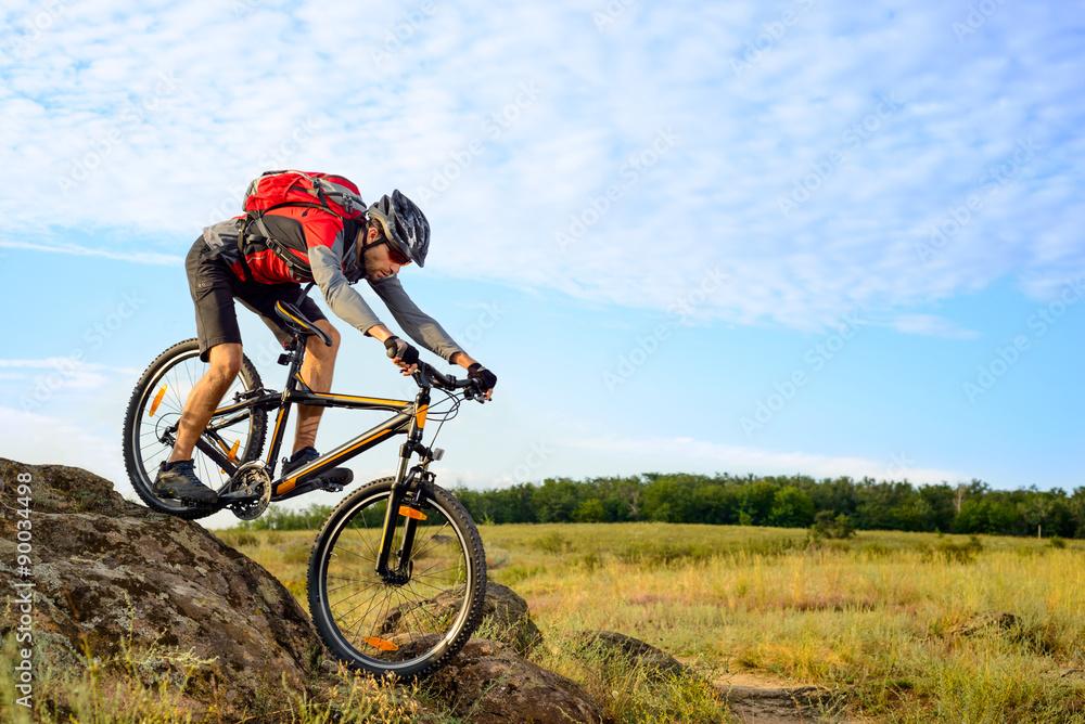 Fototapeta Cyclist Riding the Bike Down Rocky Hill