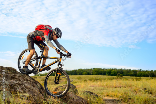 Foto  Cyclist Riding the Bike Down Rocky Hill