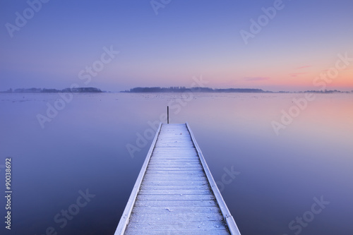 Photo Stands Lake Jetty on a still lake in winter in The Netherlands