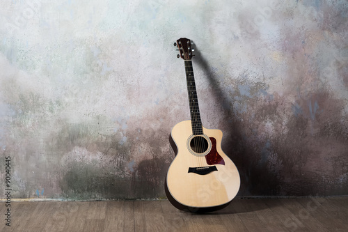Foto  The guitar stands near the wall in the style of grunge, music, musician, hobby,