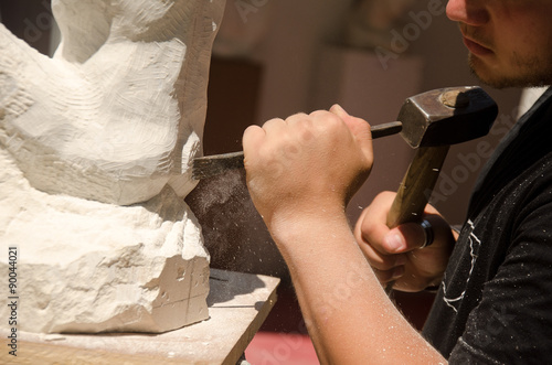 Fotografie, Obraz  Man with hammer working on stone statue