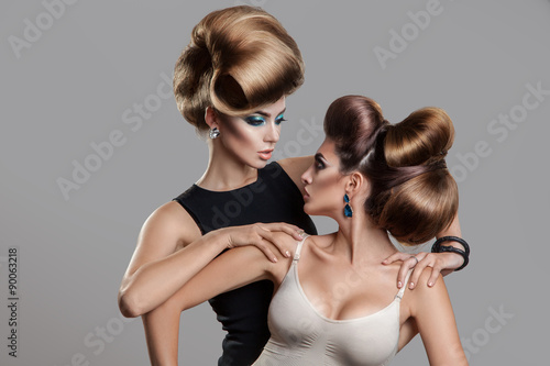 Fotobehang Kapsalon Studio photo of two beauty women with creative hairstyle looking