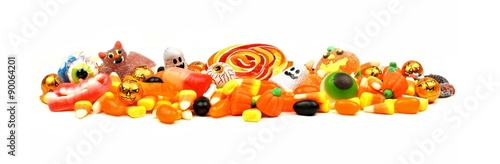 Long pile of colorful Halloween candy and sweets over a white background