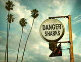 Fototapeta Młodzieżowe - aged and worn vintage photo of danger sharks sign on beach