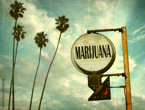 Photo  aged and worn vintage photo of marijuana sign with palm trees