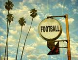 Fototapeta Młodzieżowe - aged and worn vintage photo of football sign with palm trees