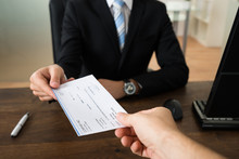 Businessman Giving Cheque To Other Person