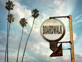 Fototapeta Młodzieżowe - aged and worn vintage photo of boardwalk sign on beach