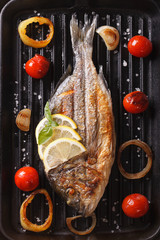 Panel Szklany Podświetlane Grill dorado fish with vegetables closeup on the grill. Vertical top view
