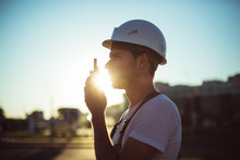 Engineer Builder Using A Walkie Talkie Giving Instructions At A Construction Site. Sunset Time.