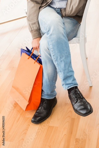 Fototapeta Man with shopping bags sitting and waiting obraz na płótnie