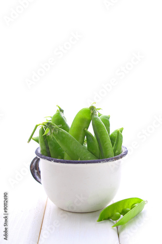 Spoed Foto op Canvas Cactus young green peas in a metal colander on a white background