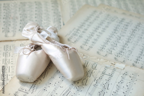 obraz dibond Ballet shoes laying on the old piano musical notes