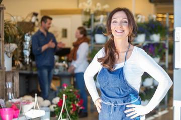 Portret nasmiješene ženske vlasnice u cvjećarnici