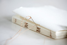 Needle And Notepad Papers On Table