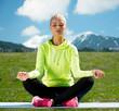 woman sitting in lotus pose doing yoga outdoors