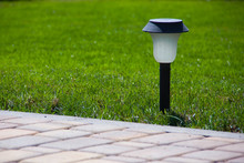 Solar Lantern Is On The Green Lawn Next To A Paved Garden Path
